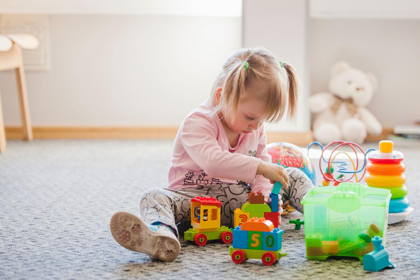 Una bimba gioca su un tappeto della sua stanza luminosa