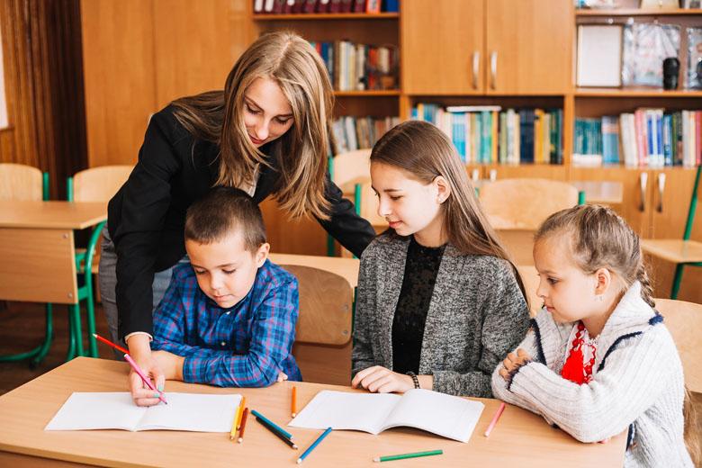 Una giovane operatrice aiuta un gruppo di bambini a svolgere i compiti scolastici