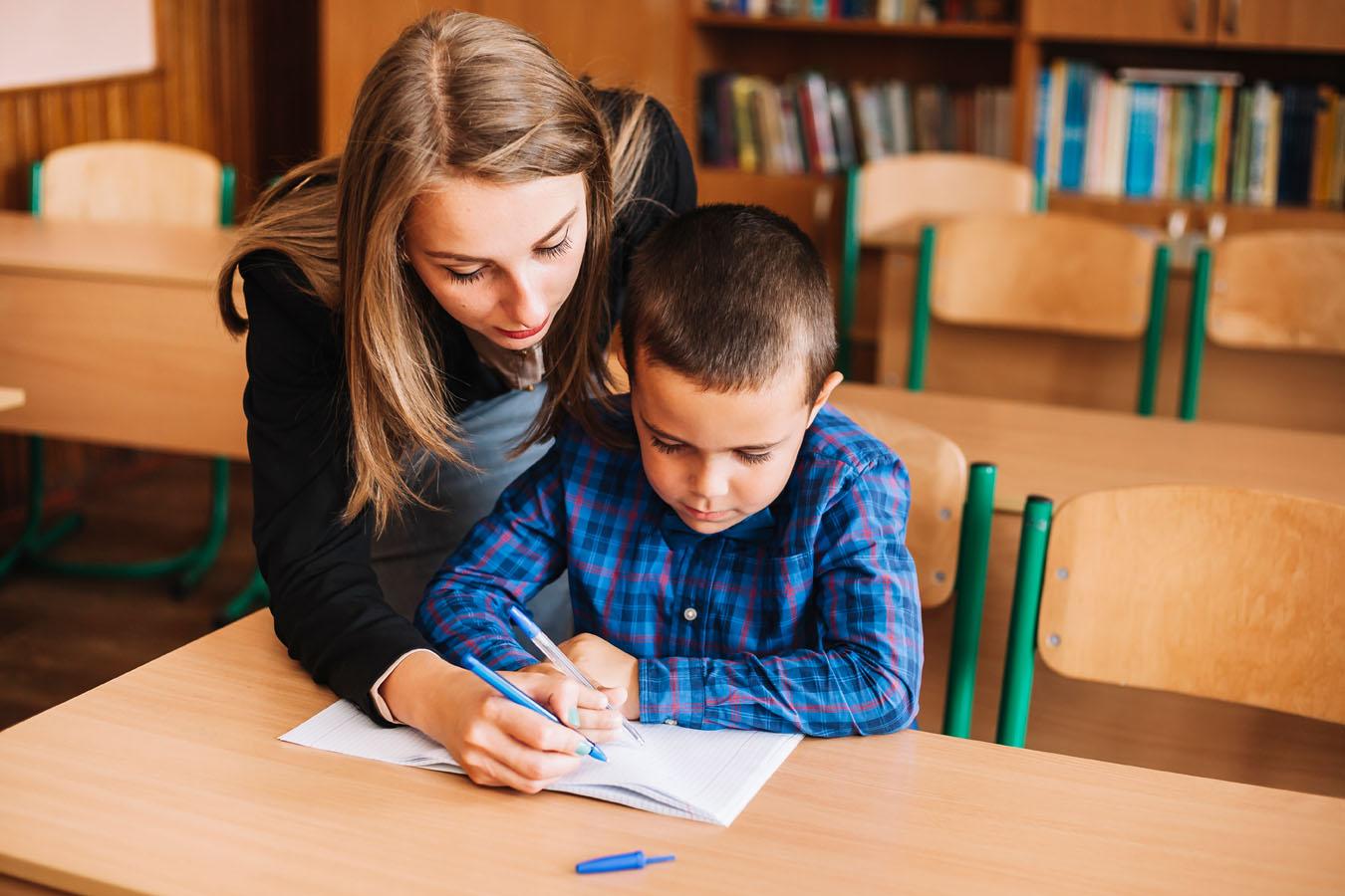 Un'operatrice aiuta un bambino a svolgere i compiti scolastici