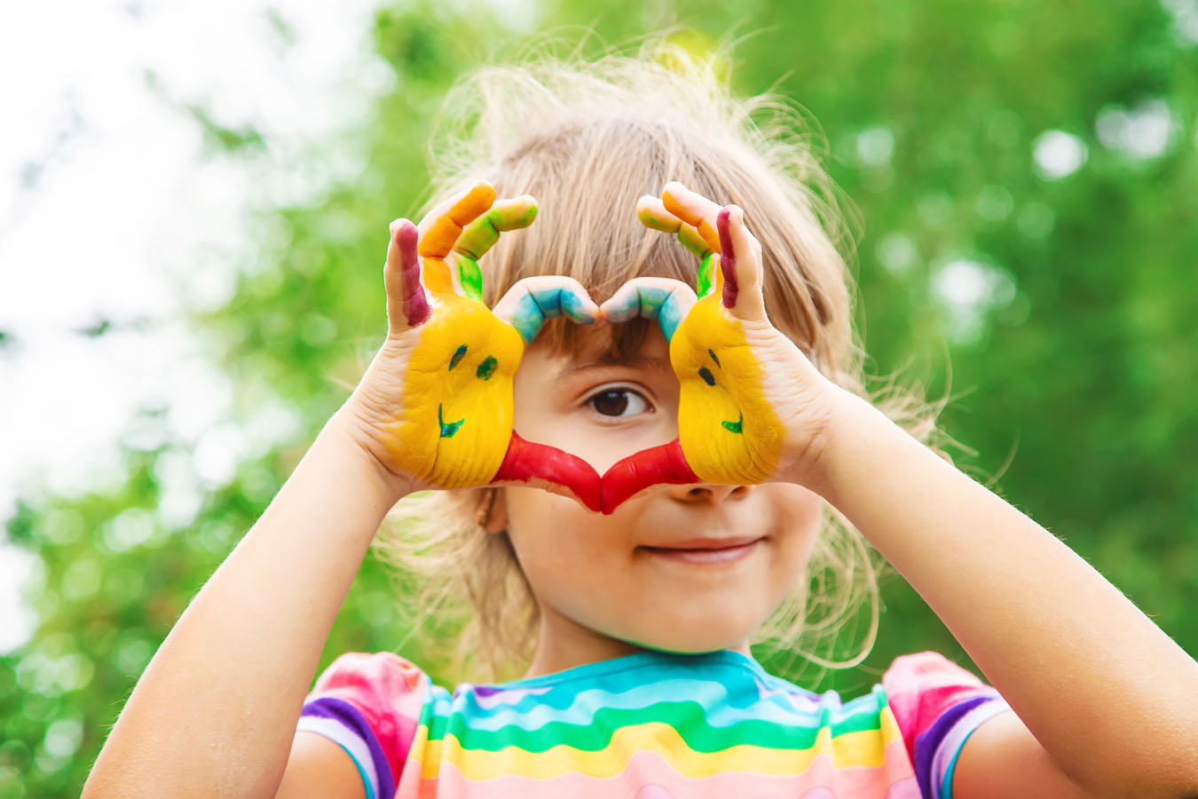Una bambina forma un cuore con le sue mani dipinte