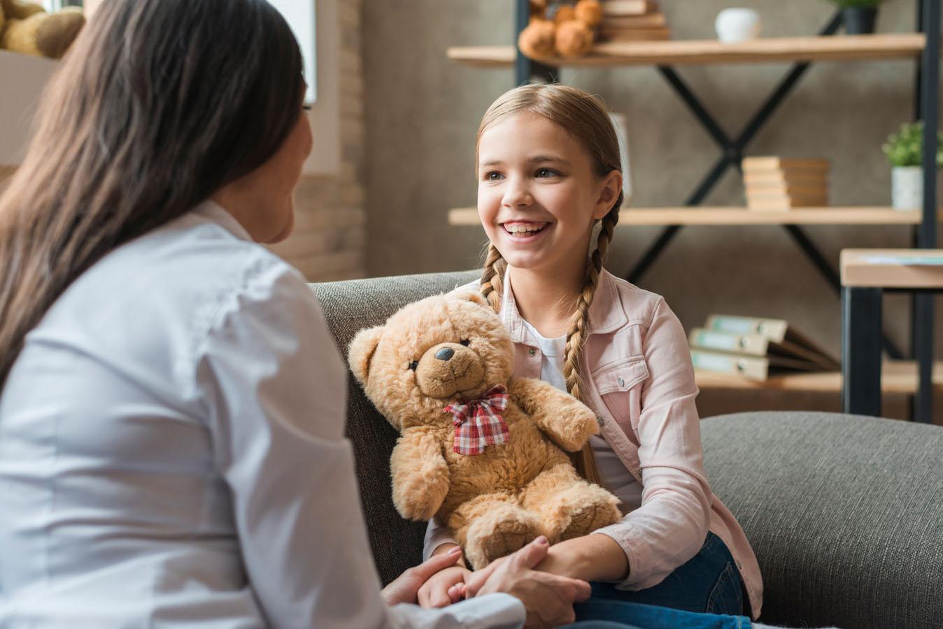Una psicologa e una bambina conversano seduti su un divano