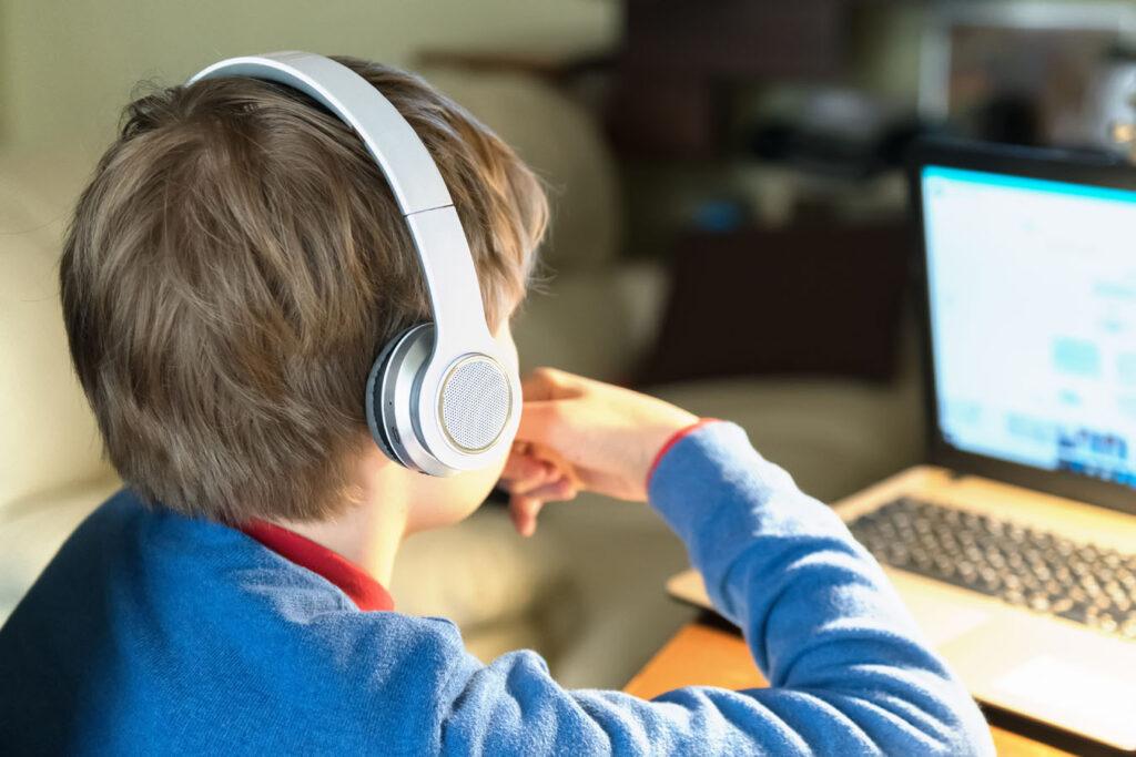 Un bambino con le cuffie gioca al computer