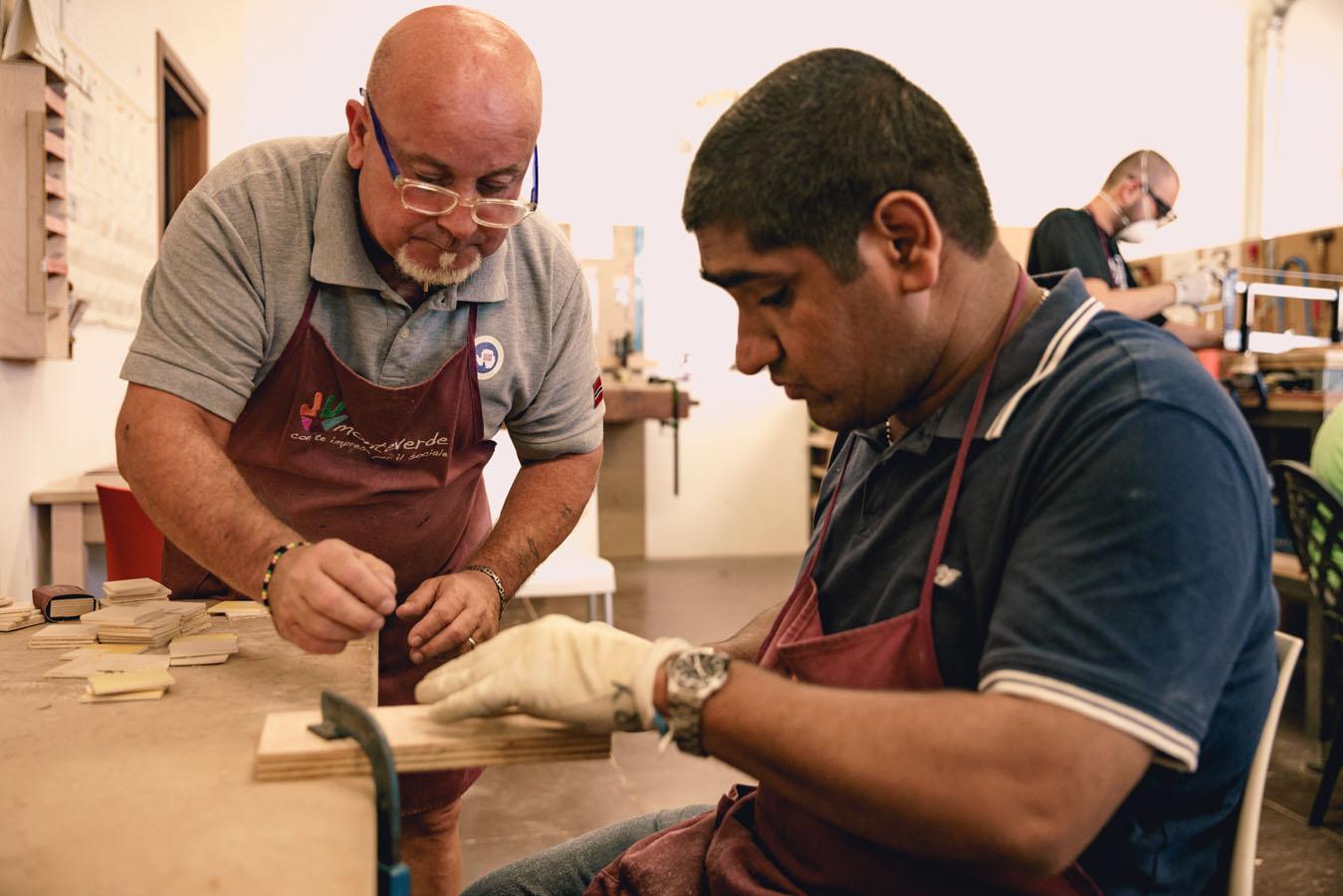 Un operatore insegna ad un ragazzo a svolgere un lavoro di falegnameria