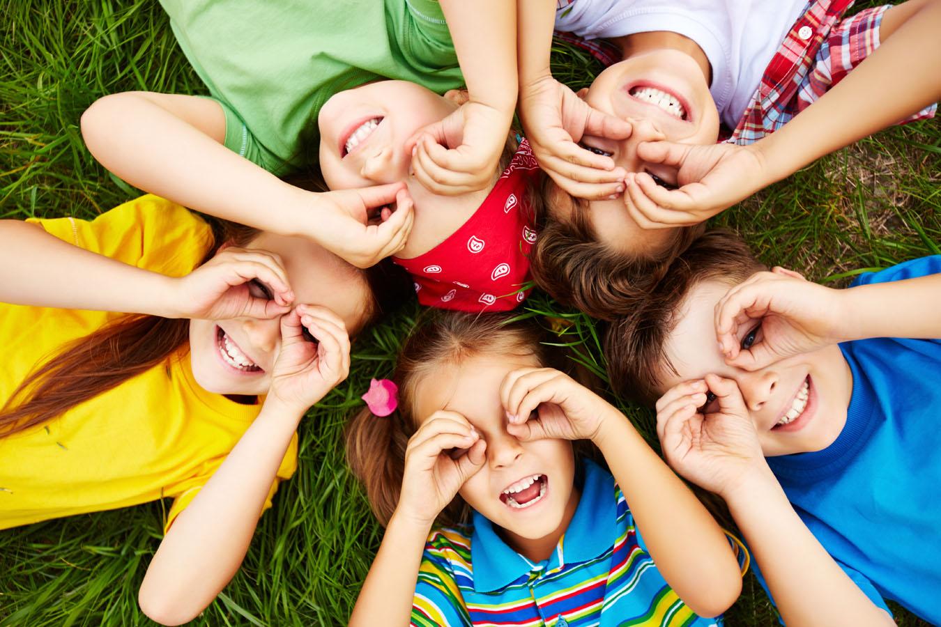 Un gruppo di bambini giocano distesi in cerchio su un prato