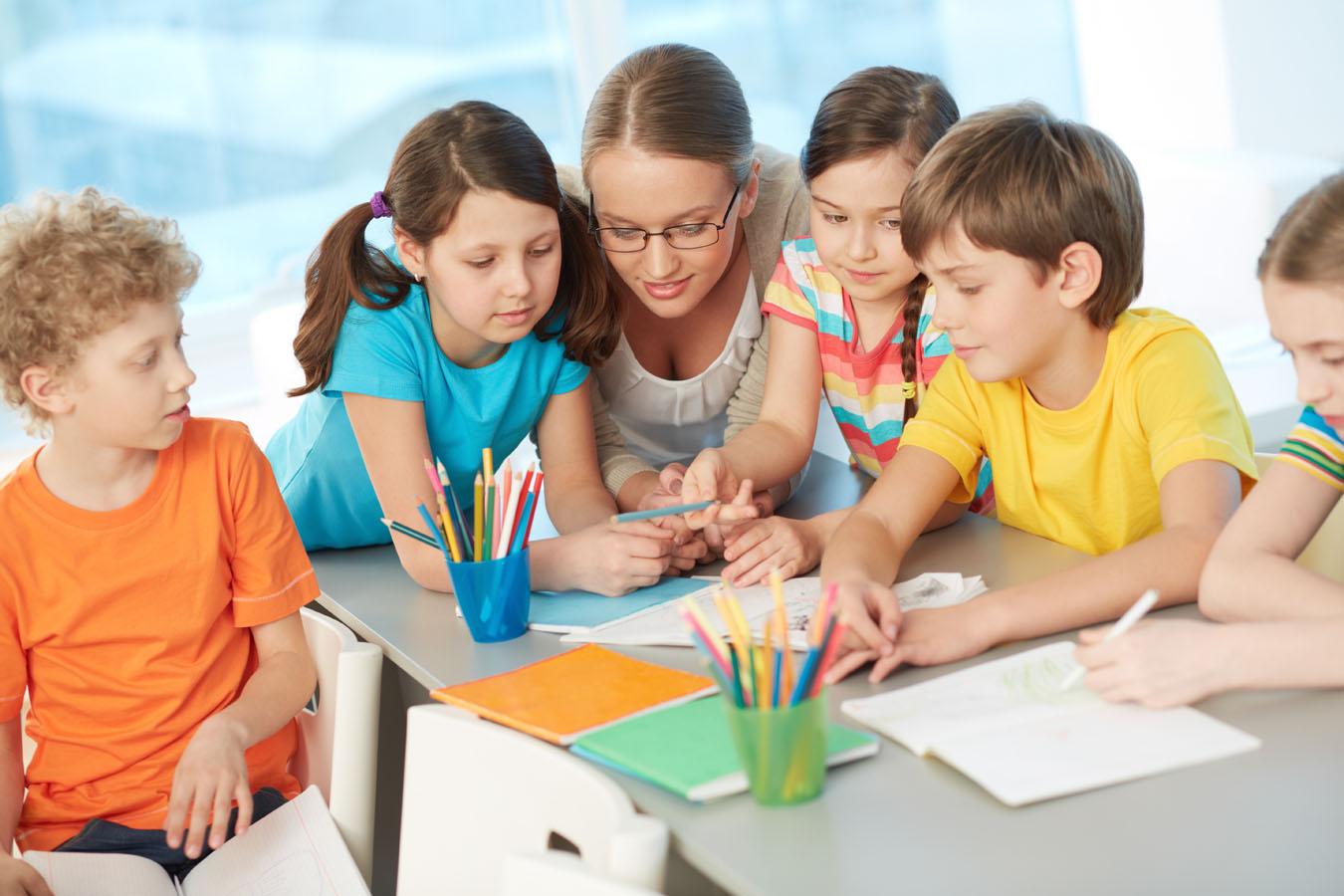 Una giovane operatrice colora dei disegni insieme al suo gruppo di bambini