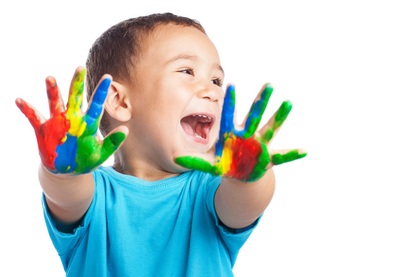 Un bambino sorridente mostra le sue mani dipinte